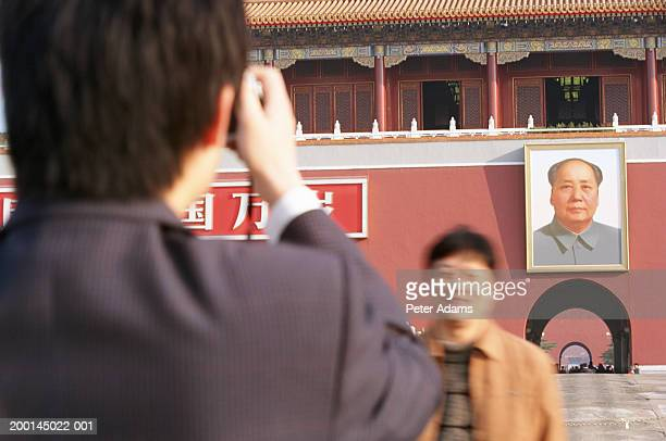 China, Beijing, Tiananmen Square, man taking photograph of friend