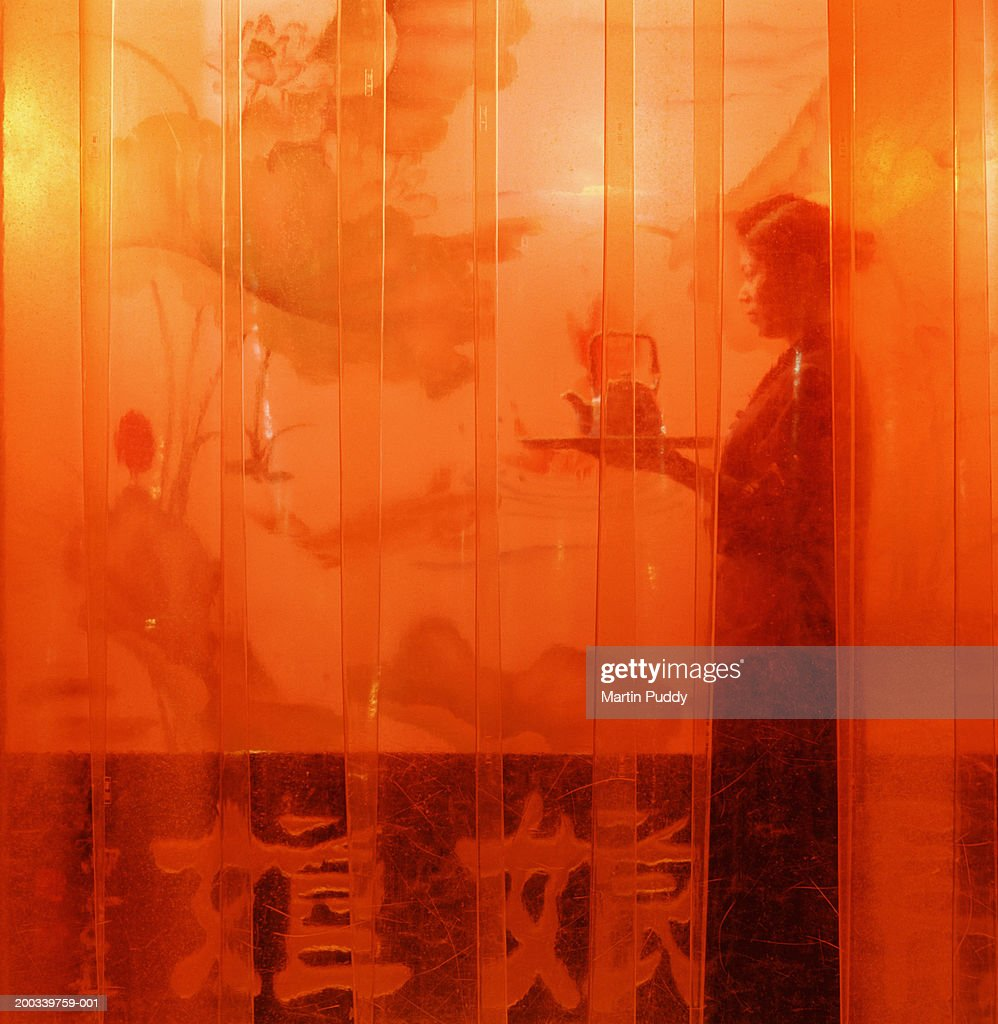China, Beijing, waitress holding tray and tea pot in tea house : Stock Photo