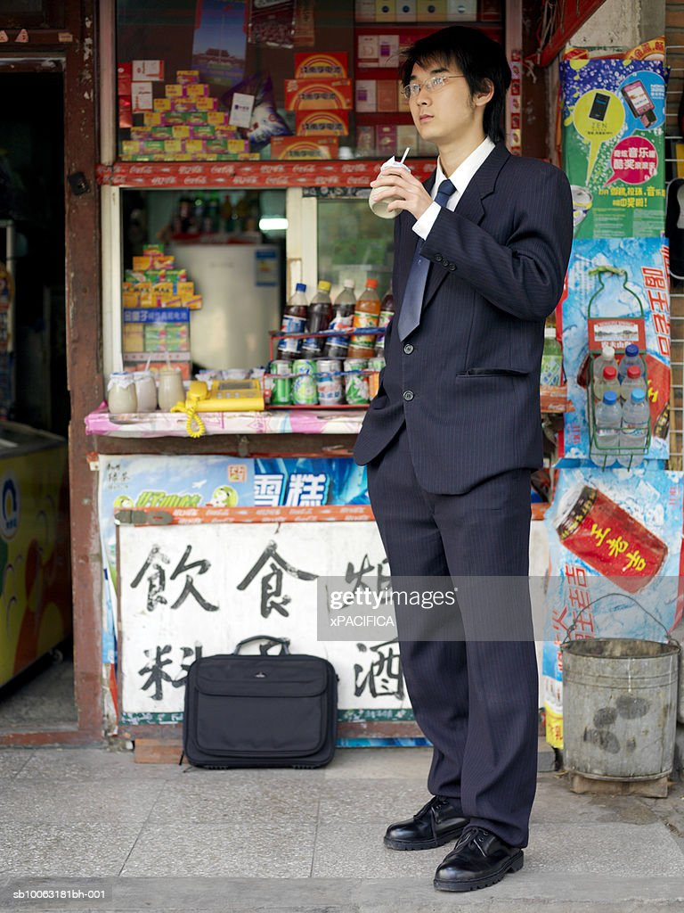 China, Beijing, young business man drinking in front of kiosk : Stock Photo