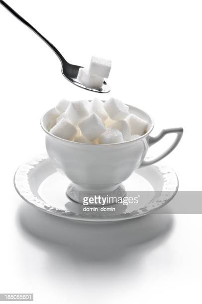 China cup full of sugar cubes with spoon isolated