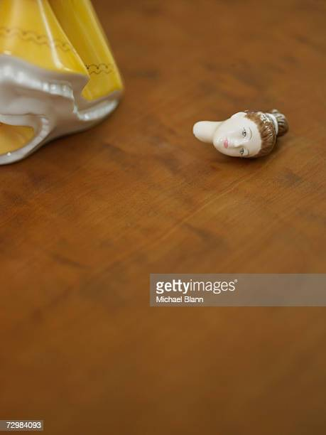 China doll with broken head on wooden surface