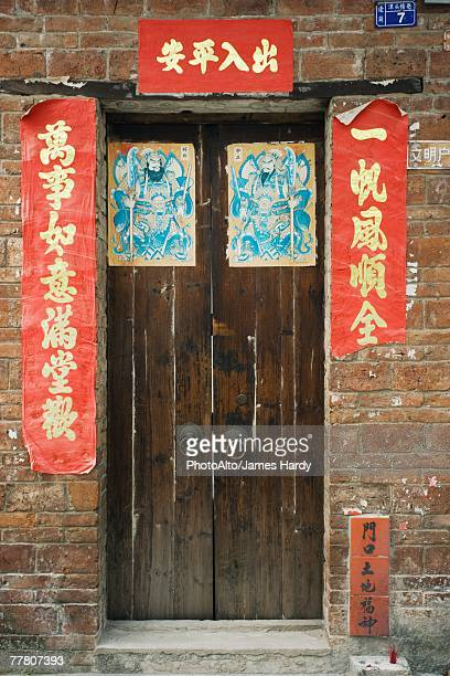 China, doorway surrounded with banners with Chinese proverbs