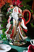 China Father Christmas ornament holding staff and garland amid festive display