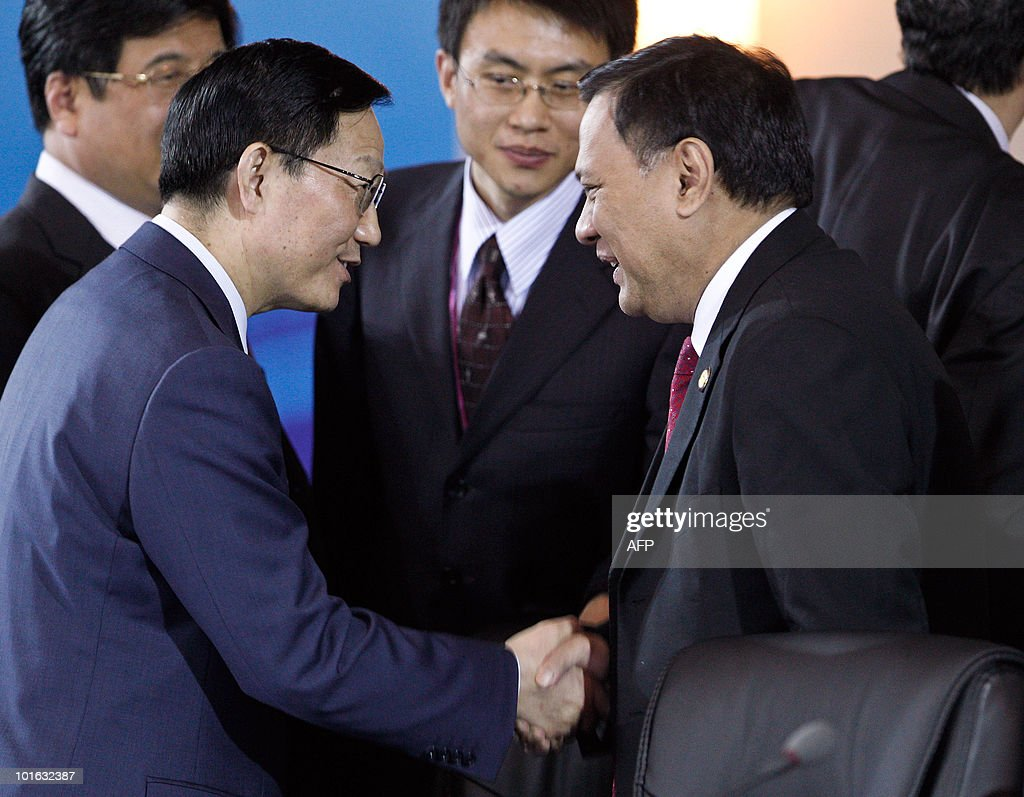 China Finance Minister Xie Xuren (L) shakes hands with an unidentified delegate during a coffee break at the G20 Finance Ministers and Central Bank Governors Meeting in Busan on June 5, 2010. Finance ministers from the world's leading nations sought to narrow differences on key banking reforms, wrapping up a two-day meeting aimed at safeguarding fragile economic recovery.