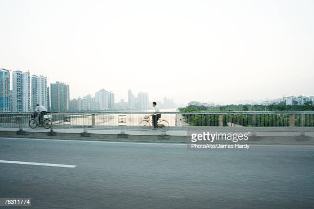 China, Guangdong Province, Guangzhou, cyclists crossing bridge, skyscrapers in distance