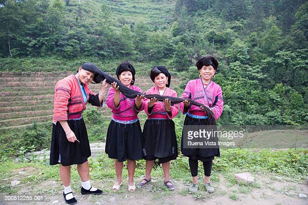 China, Guangxi Province, women holding out woman's hair to be combed