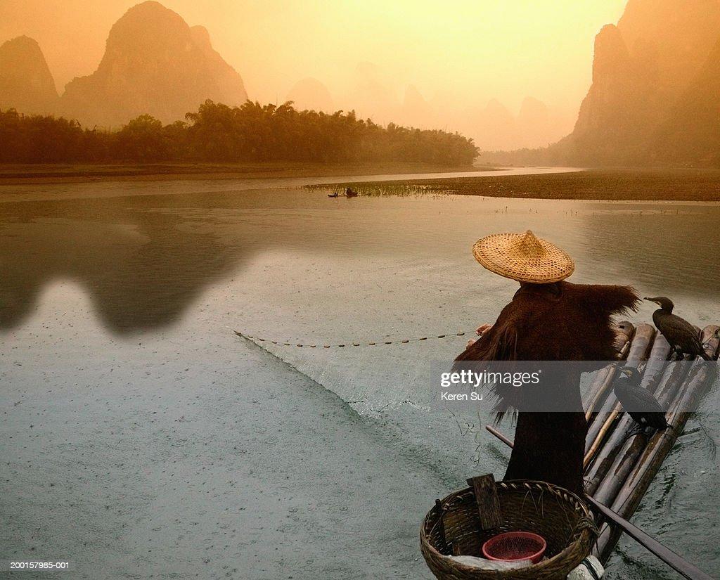 China, Guangxi, Yangshuo, fisherman casting net from bamboo raft, dawn