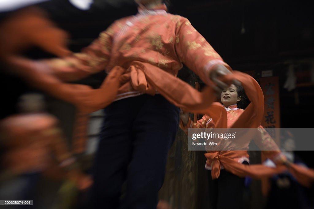 China, Guizhou, young women dancing at festival (blurred motion)
