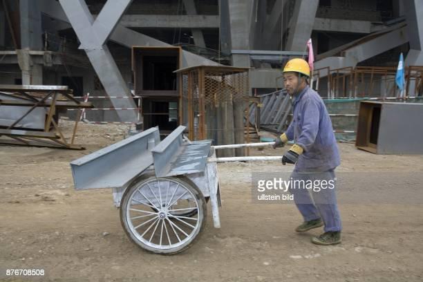 China Hebei Beijing Sommerolympiade 2008 Blick auf die Baustelle des Nationalstadions Bauarbeiter transportiert Stahlbauteile auf dem Handkarren  ...