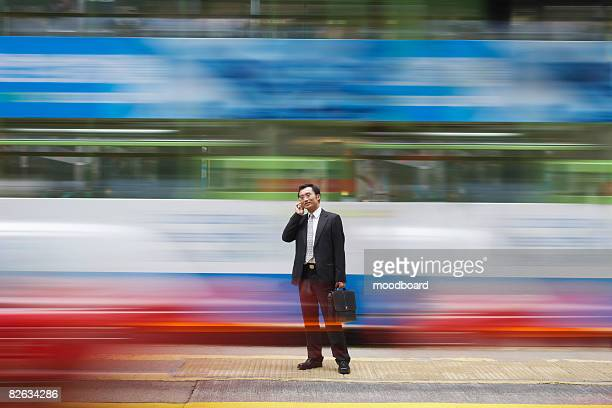 China, Hong Kong, business man using mobile phone, standing on street, long exposure