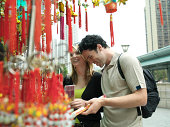 China, Hong Kong, couple looking at incense by Po Lim Temple