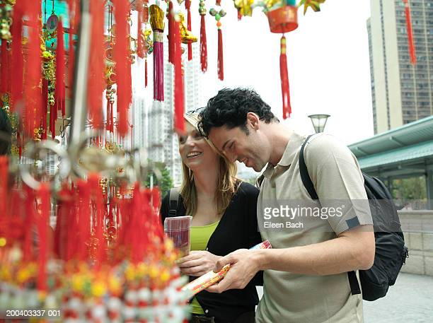 China, Hong Kong, couple looking at incense by Po Lim Temple