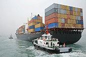 China, Hong Kong Harbor, tugboat sailing alongside container ship