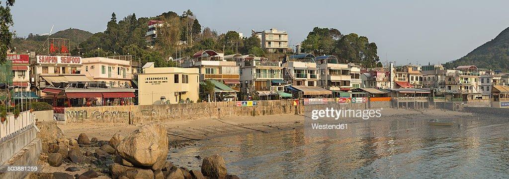 China, Hong Kong, Lamma Island, waterfront with houses and boat in Yung Shue Wan bay