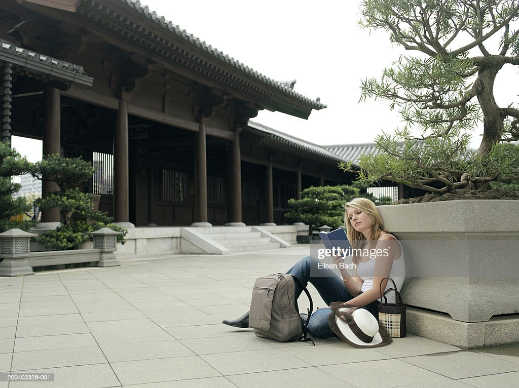 China, Hong Kong, Po Lin Monastery, woman reading book