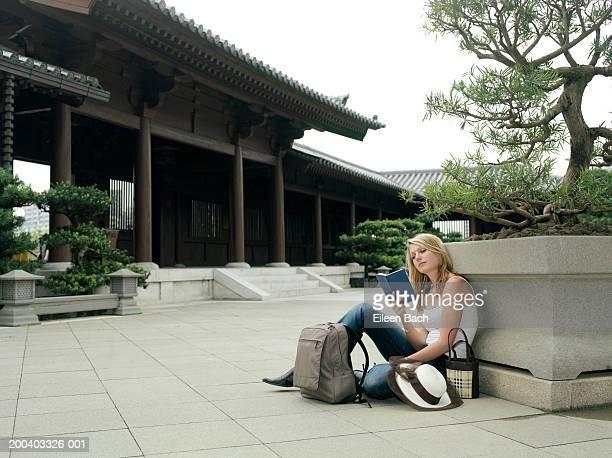 China, Hong Kong, Po Lin Monastery, woman reading book