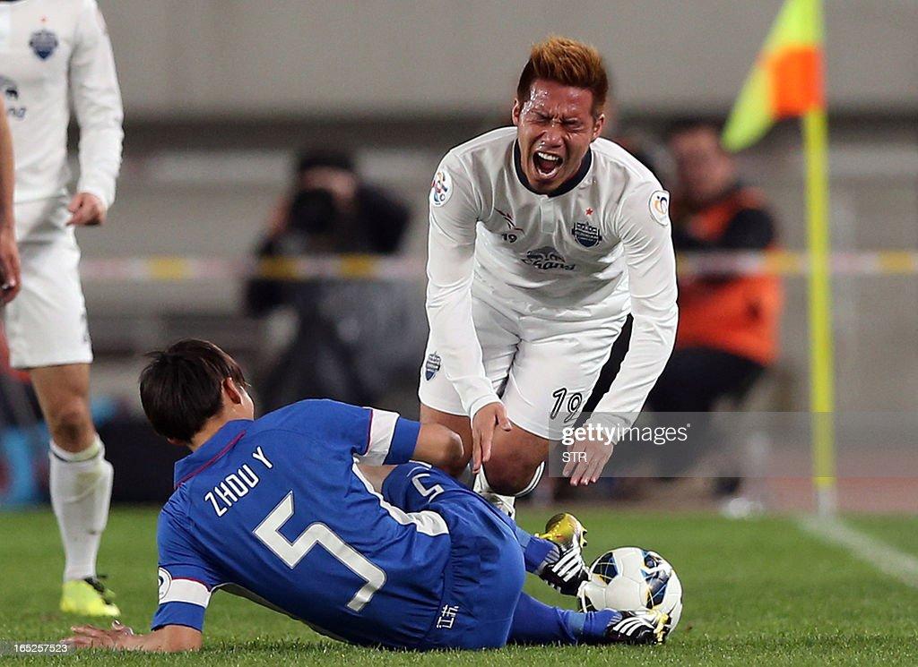 China Jiangsu Sainty's Zhao Yun (L) takes down Thailand Buriram United's Kai Hirano during the AFC Champions League group E match at the Olympic Sports Center in Nanjing, east China's Jiangsu province on April 2, 2013. Jiangsu beat Buriram 2-0.