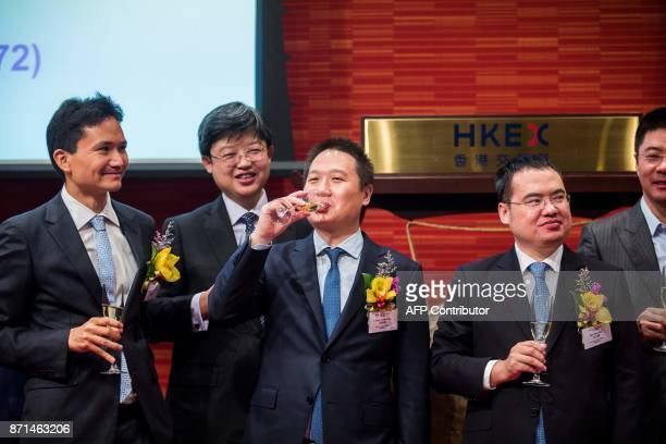 China Literature Limited CoChief Executive Officers Liang Xiaodong sips champagne while Wu wenhui looks on at the companies Intial Public Offering at...