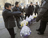 DANDONG China North Korean men on their way back to North Korea buy flowers in front of a customs house in Dandong Liaoning Province in China on the...