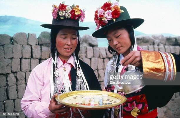 China Qinghai Province Huzhu County Women of Tu nationality and Lamaist Buddhist Yellow Hat sect preparing traditional welcome of three small glasses...