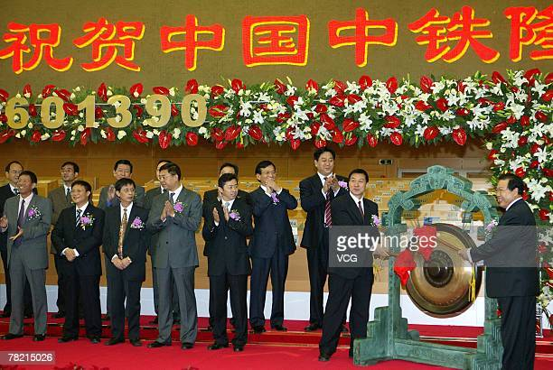 China Railway Chairman Shi Dahua hits the gong during a ceremony to mark China Railway Group's listing at the trading hall of the Shanghai Stock...
