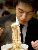 China, Shanghai, businessman eating noodles in restaurant