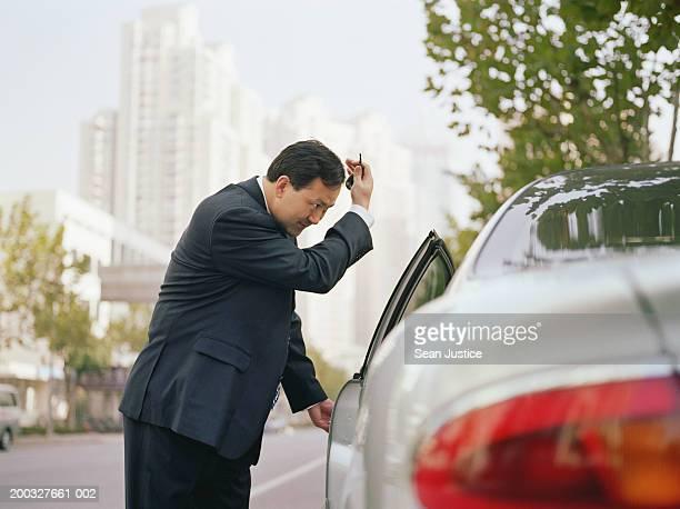 China, Shanghai, businessman opening car door, smoothing hair