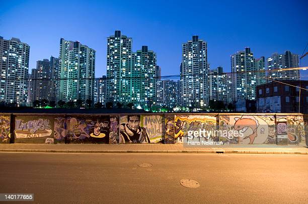 China, Shanghai, district of Puxi, wall with graffiti and skyline at night