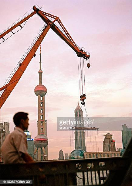 China, Shanghai, man walking on Bund near crane with Pudong skyline in background
