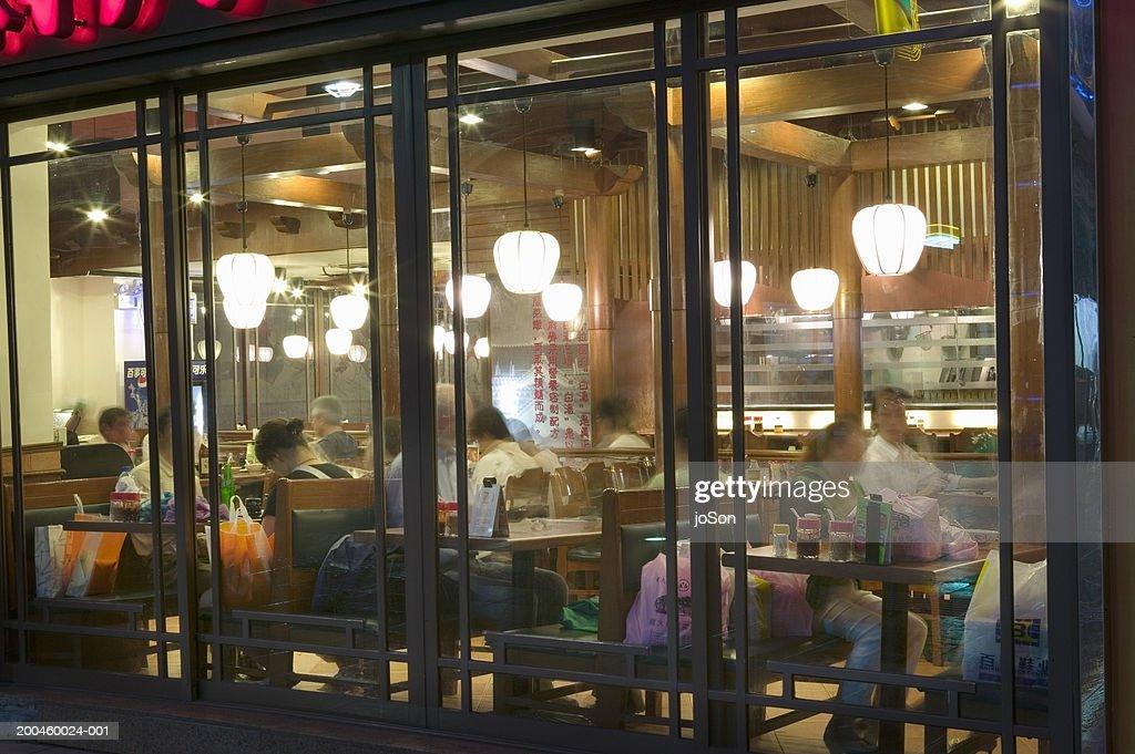 China, Shanghai, people in cafe at night (long expsosure) : Stock Photo