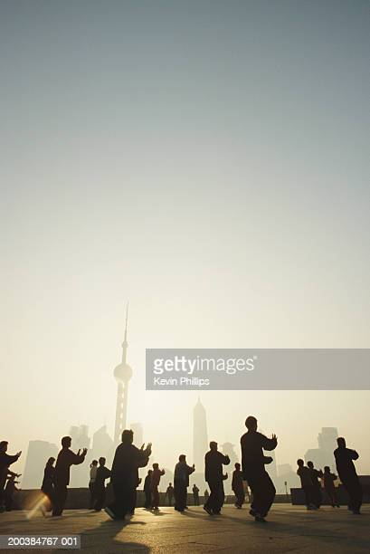 China, Shanghai, people practicing T'ai chi at dawn, outdoors