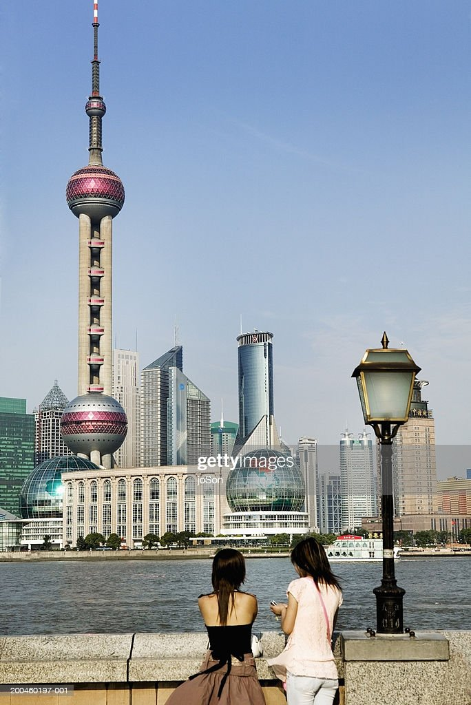 China, Shanghai, two people facing Pudong skyline, rear view : Stock Photo