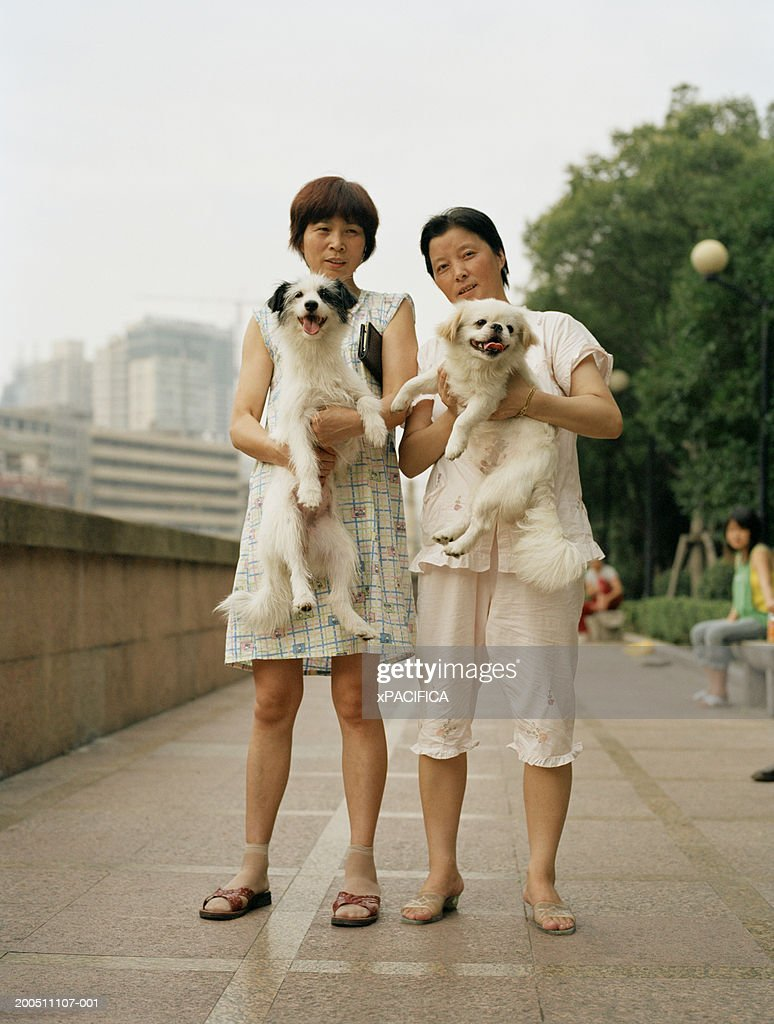 China, Shanghai, two women holding up dogs, portrait : Stock Photo