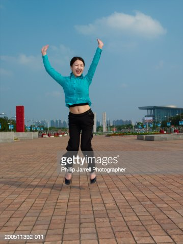 China, Shanghai, woman jumping, arms raised, smiling : Stock Photo