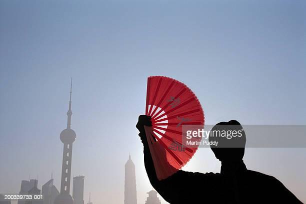 China, Shanghai, woman practicing t'ai chi, holding fan, sunrise