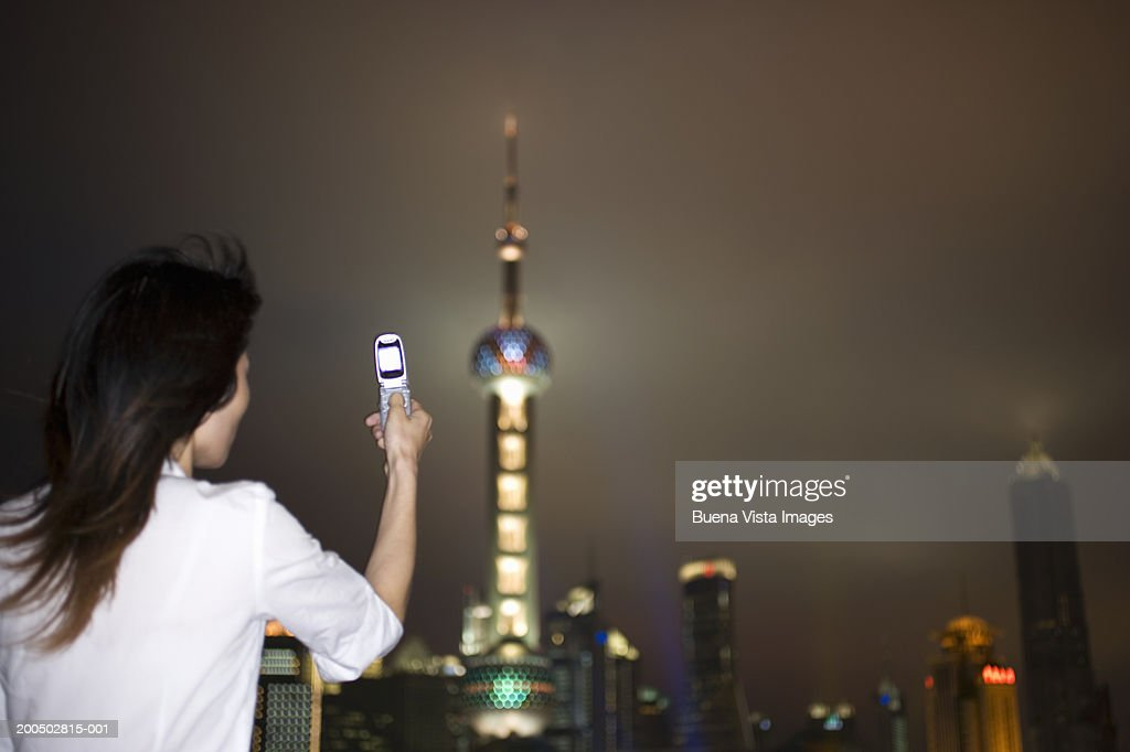 China, Shanghai, young woman photographing Oriental Pearl Tower, night : Stock Photo