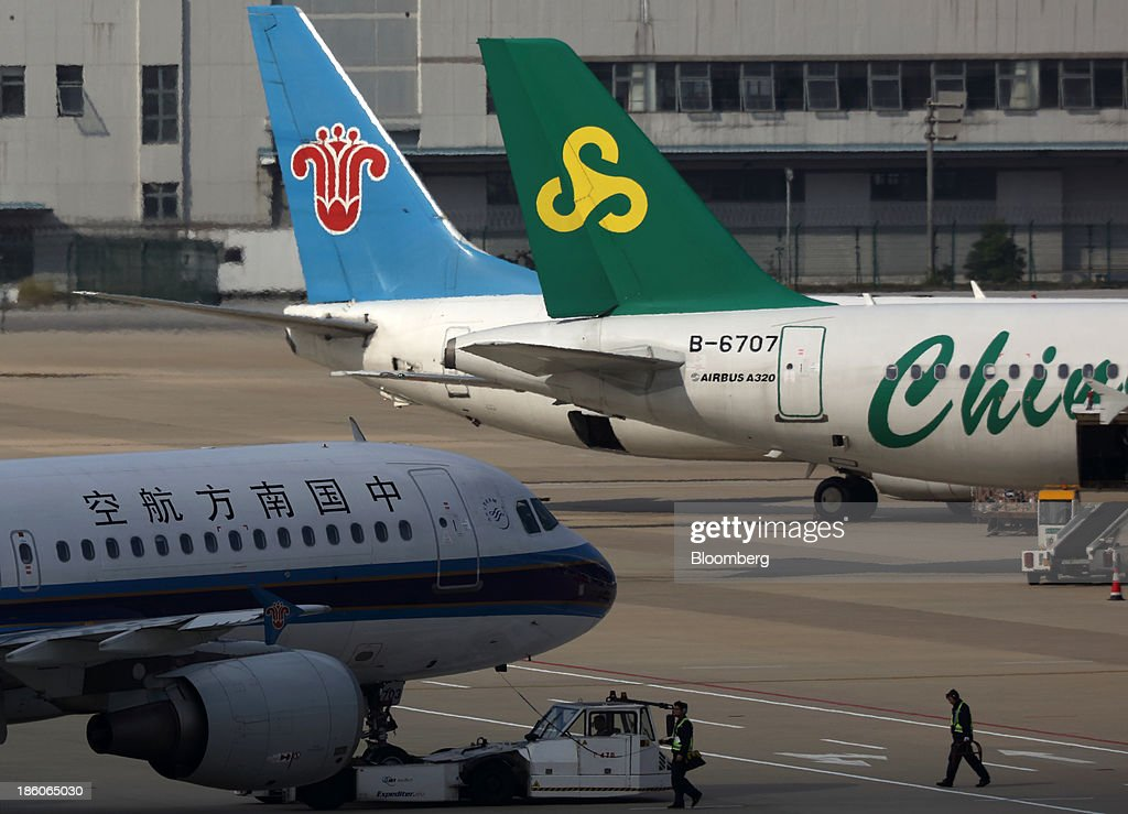 A China Southern Airlines Co. aircraft, left, taxies past a Spring Airlines Co. aircraft, right, at Shanghai Pudong International Airport in Shanghai, China, on Saturday, Oct. 26, 2013. Airline profits worldwide in 2013 will be 7.9 percent smaller than estimated at $11.7 billion amid sluggish travel demand and rising oil prices tied to the Syria crisis, the International Air Transport Association said last month. Photographer: Tomohiro Ohsumi/Bloomberg via Getty Images