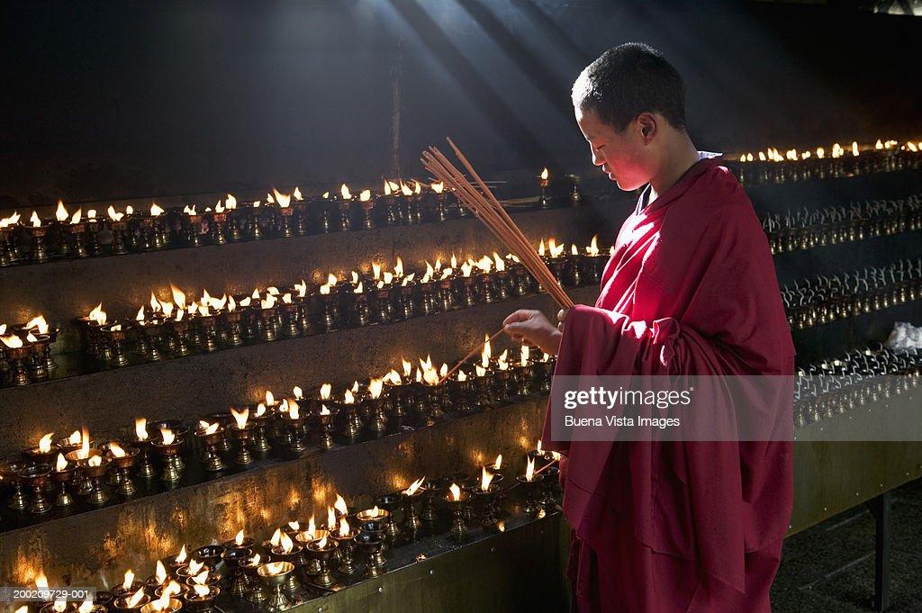 China, Tibet, Buddhist monk lighting insense at Jokhang monastery