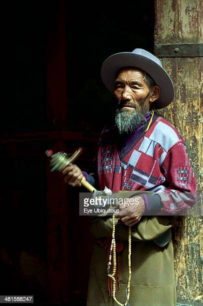China Tibet Lhasa Portrait of a man spinning a mini Prayer Wheel at the Jokhang Temple