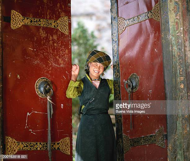 China, Tibet, Lhasa, woman at open door smiling, portrait