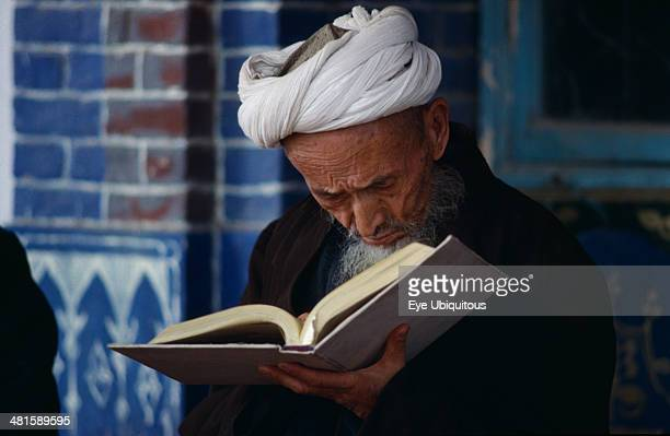 China Xinjiang Province Religion Imam Holy man with head down reading in mosque