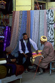 China Xinjiang Province Turfan Market Scene Uigur Men Fabric Store