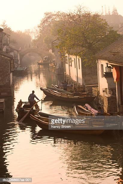 China, Zhou Zhuang, man in boat on canal