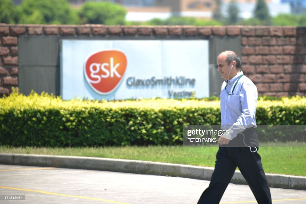 China-Britain-corruption-pharmaceutical-GSK by Bill SAVADO Photo taken on July 23, 2013 shows a pedestrian walking past British pharmaceutical giant GlaxoSmithKlines factory in Shanghai. Beijing's targeting of GlaxoSmithKline in a high-profile bribery probe is a reminder of the risks foreign companies face when seeking the huge rewards of China's market, analysts say. AFP PHOTO/Peter PARKS