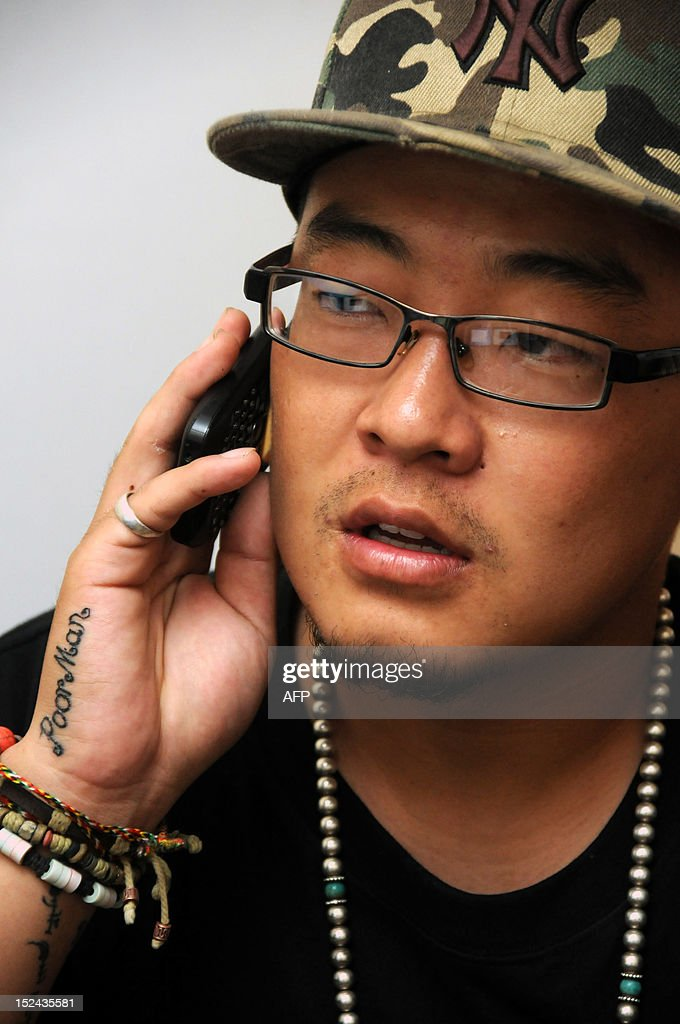 STORY 'China-culture-music,FEATURE' BY TOM HANCOCK This picture taken on August 21, 2012, shows rapper Sodmuren of hip-hop band 'Poorman', making a phone call in Hohhot, north China's Inner Mongolia region. Members of China's Mongolian ethnic minority, whose ancestors were first united by Genghis Khan, are turning to hip hop to condemn the resources boom they say is wreaking havoc on their traditions and lands -- while avoiding the authorities' attention.