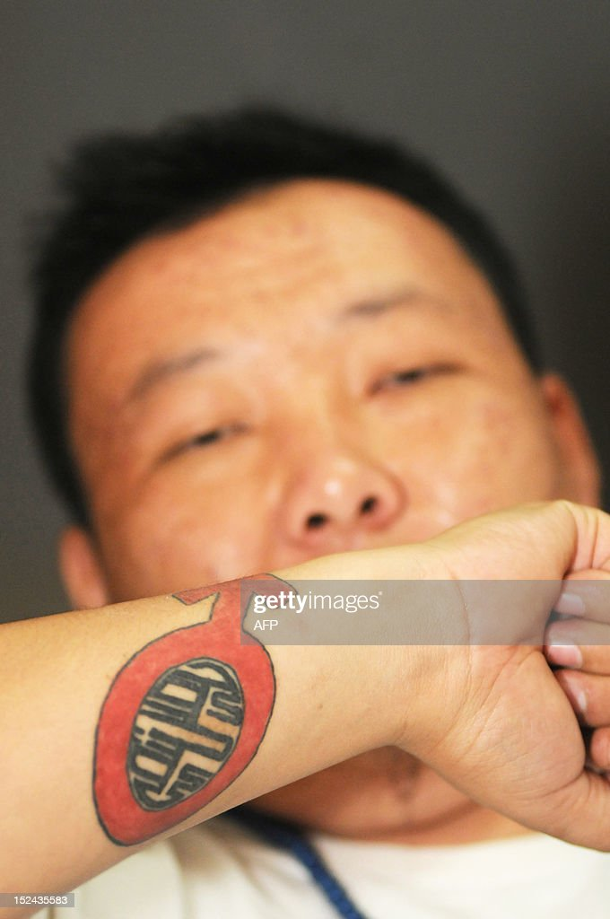 STORY 'China-culture-music,FEATURE' BY TOM HANCOCK This picture taken on August 21, 2012, shows rapper Bondoo of hip-hop band 'Poorman', displaying his tattoo on his wrist during an interview in Hohhot, north China's Inner Mongolia region. Members of China's Mongolian ethnic minority, whose ancestors were first united by Genghis Khan, are turning to hip hop to condemn the resources boom they say is wreaking havoc on their traditions and lands -- while avoiding the authorities' attention.