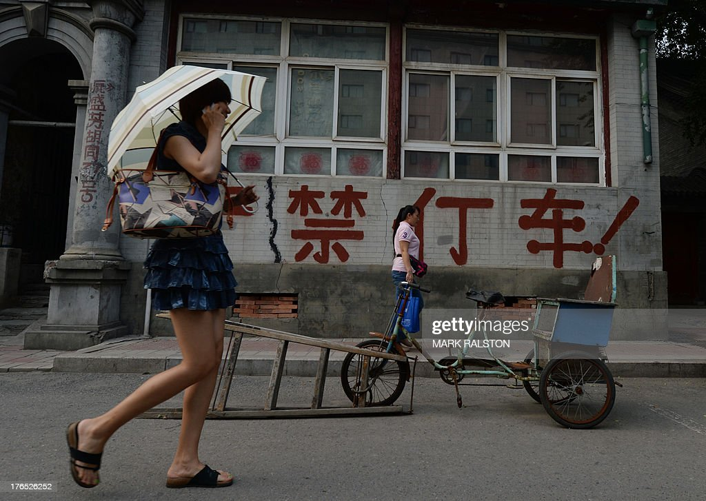 China-economy-data,ANALYSIS by Kelly OLSEN This photo taken on August 14, 2013 shows a Chinese woman walking past an old house in Beijing. China has soared almost to the top of the world's economic league tables, but whether the official data underpinning its status can be trusted is a constant headache. Simmering unease regarding China's economic figures has taken on new meaning this year with discrepancies in some statistics and questions over just how much gross domestic product (GDP) is really growing. AFP PHOTO / Mark RALSTON