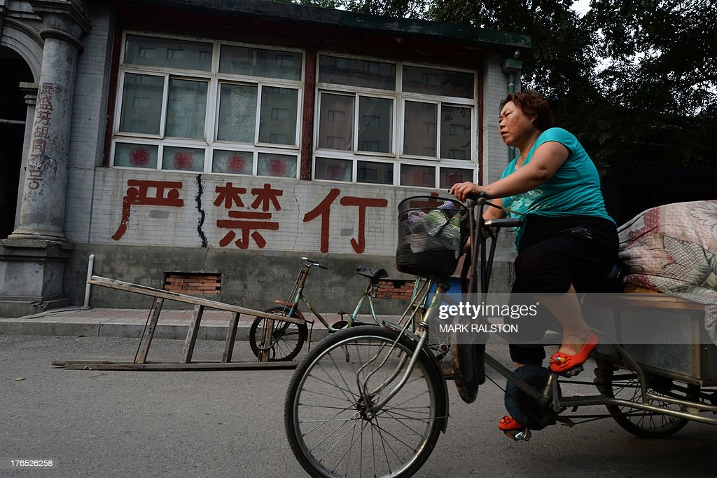 China-economy-data,ANALYSIS by Kelly OLSEN This photo taken on August 14, 2013 shows a Chinese woman cycling past an old house in Beijing. China has soared almost to the top of the world's economic league tables, but whether the official data underpinning its status can be trusted is a constant headache. Simmering unease regarding China's economic figures has taken on new meaning this year with discrepancies in some statistics and questions over just how much gross domestic product (GDP) is really growing. AFP PHOTO / Mark RALSTON