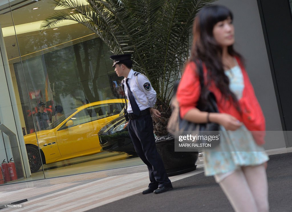 China-economy-data,ANALYSIS by Kelly OLSEN This photo taken on August 14, 2013 shows a Chinese woman walking past a luxury car dealership in Beijing. China has soared almost to the top of the world's economic league tables, but whether the official data underpinning its status can be trusted is a constant headache. Simmering unease regarding China's economic figures has taken on new meaning this year with discrepancies in some statistics and questions over just how much gross domestic product (GDP) is really growing. AFP PHOTO / Mark RALSTON
