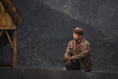 ChinaeconomyenvironmentcoalclimateFOCUS by Tom HANCOCK In this photo taken on November 20 a worker rests near a pile of coal near a coal mine at...